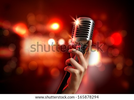 Female hand holding a single retro microphone against colourful background - stock photo