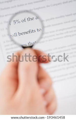 Female hand holding a small magnifying glass over the benefits section of a document or contract. - stock photo
