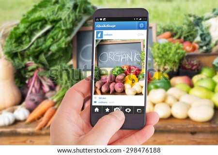 Female hand holding a smartphone against table of fresh produce at market - stock photo