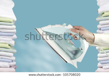 Female hand holding a steam iron surrounded by columns of freshly ironed clothes. - stock photo