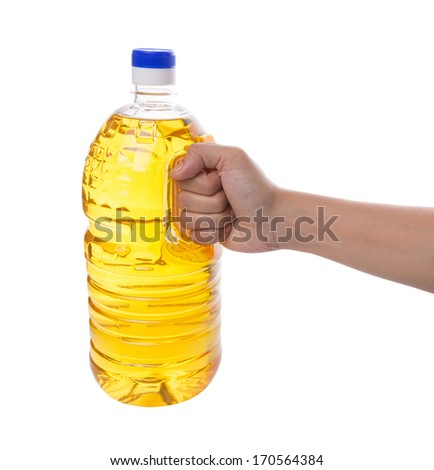 Female hand holding a vegetable cooking oil in a plastic container over white