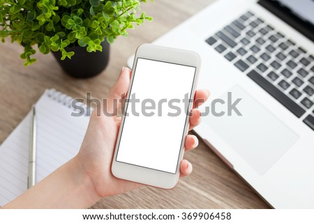 female hand holding a white phone with isolated screen on a table with laptop - stock photo