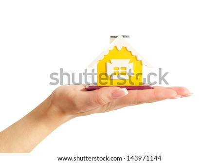 female hand holding a yellow house - stock photo