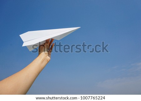 Female hand holding aircraft paper  on the blue sky background with success,gold,meaning to you business.