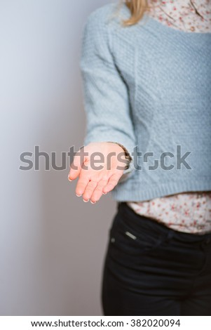 Female hand holding an invisible object on gray background