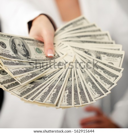 Female hand holding and sharing stack of 100 dollar banknotes - stock photo