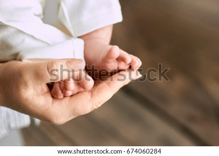 Female hand holding baby feet. Legs of child close up. Life and motherhood.