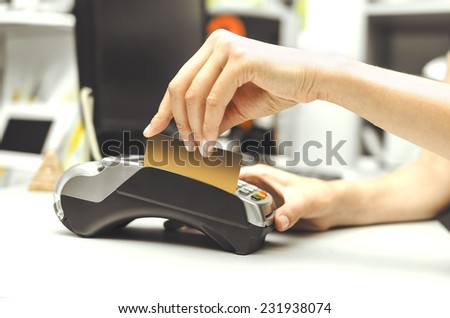 Female hand holding bank terminal and card - stock photo