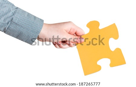 female hand holding big yellow paper puzzle piece isolated on white background