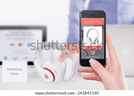 Female hand holding black mobile smart phone with nfc smart pay application.  Blurred store with seller and gadgets on the background. Purchase of headphones by fingerprint scanning in smart pay app. - stock photo