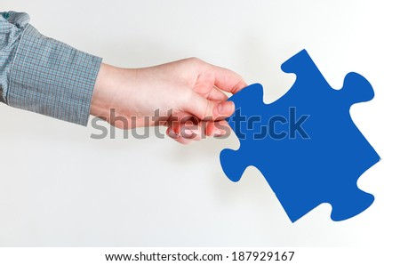 female hand holding blue puzzle piece on grey background