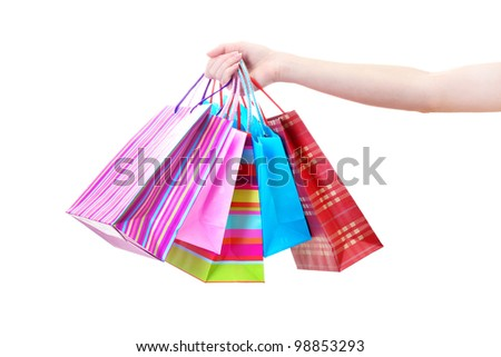 Female hand holding bright shopping bags isolated on white