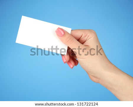 Female hand holding business card, on color background - stock photo
