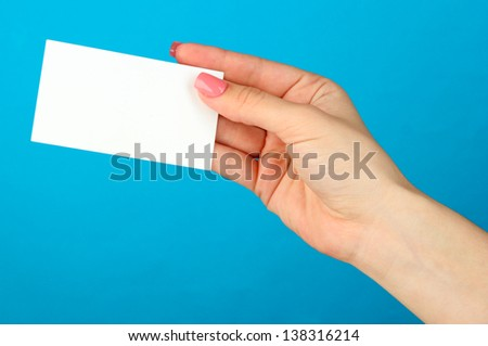 Female hand holding business card, on color background