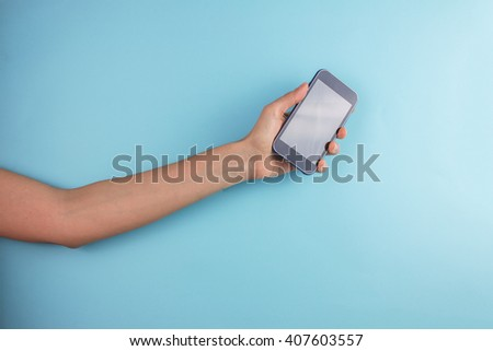 Female Hand Holding Cell Phone on Blue Background.