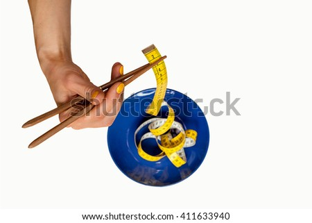 Female hand holding  chinese chopsticks and plate with measure tape isolated on white background - stock photo