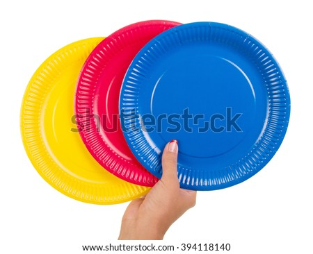 Female hand holding colorful disposable plates isolated on white background. - stock photo