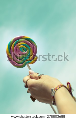 Female hand holding colorful spiral lollipop over blue sky  - stock photo
