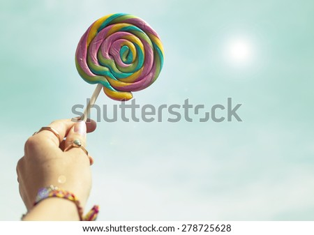 Female hand holding colorful spiral lollipop over sky / Dreams hope concept, copy space for your text / Retro style image - stock photo