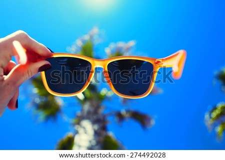 Female hand holding colorful sunglasses against palm tree and blue sunny sky, summer vacation holidays concept, first person shot, looking though glasses - stock photo