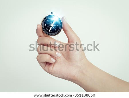female hand holding compass - stock photo