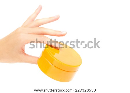 Female hand holding container with cream or scrub in isolation - stock photo