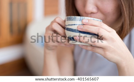 Female hand holding cup of coffee in coffee shop