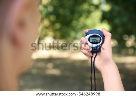 Female hand holding digital stopwatch, close up