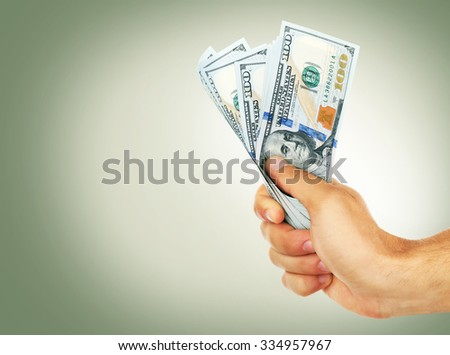 Female hand holding dollars on green background