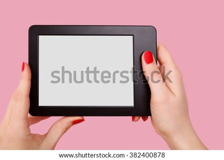 Female hand holding e reader isolated on pink background. Reading, education and learning concept.  - stock photo