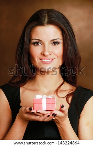 Female hand holding gift box isolated on brown background - stock photo