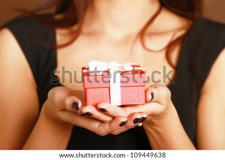 Female hand holding gift box isolated on red background - stock photo
