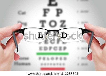 Female hand holding glasses with eyesight test on chart board.