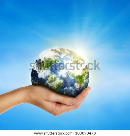 female hand holding globe over blue sky - environment protection and travel concept -Elements of this image furnished by NASA - stock photo
