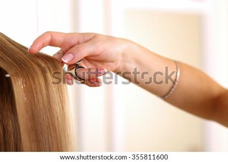 Female hand holding golden scissors and lock of long straight blonde hair closeup. Hairdresser salon, barber shop, perfect look, modern technique, new hairdo concept
