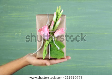 Female hand holding natural style handcrafted gift box with fresh flowers and rustic twine, on wooden background - stock photo