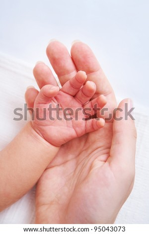 Female hand holding newborn baby's hand - stock photo
