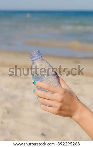 Female hand holding opened bottle of water against beach background - stock photo