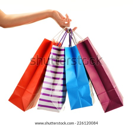 Female hand holding paper shopping bags isolated on white background - stock photo