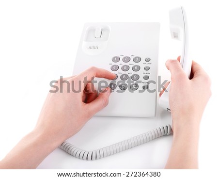 Female hand holding phone receiver and dialing number isolated on white - stock photo