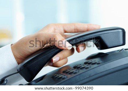 Female hand holding phone receiver over telepnone - stock photo