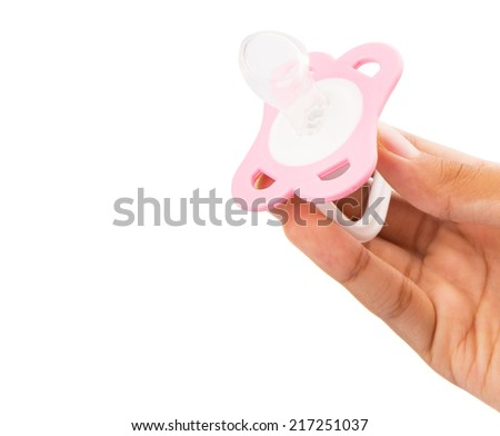 Female hand holding pink pacifier over white background