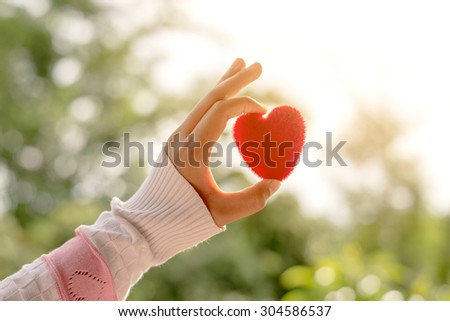 Female hand holding red heart up to the sun during morning with a vintage , love and valentine concept