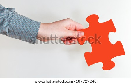 female hand holding red puzzle piece on grey background