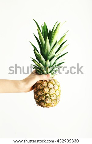 Female hand holding ripe pineapple on a white background - stock photo