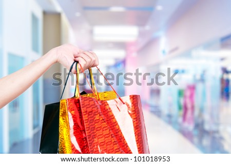 Female hand holding shopping bags in a shopping center