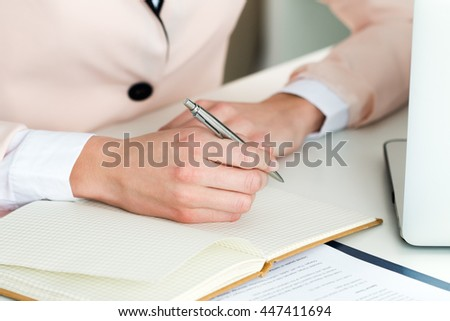 Female hand holding silver pen closeup. Woman writing letter, list, plan, making notes, doing homework. Online distant education, freelance, self development and perfection concept
