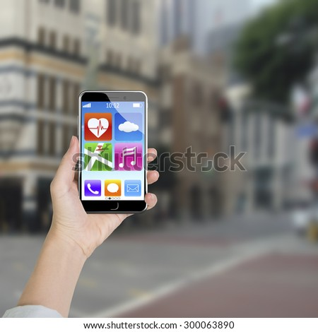 Female hand holding smart phone with colorful app icons, blur street background. - stock photo