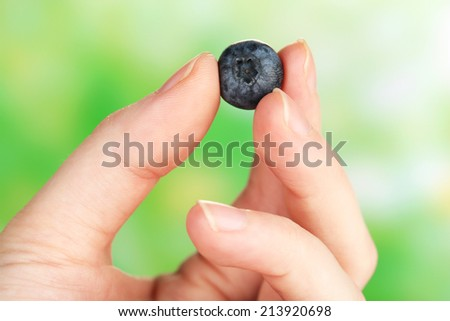 Female hand holding tasty ripe blueberry on nature background