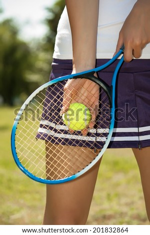 Female hand holding tennis racket - stock photo